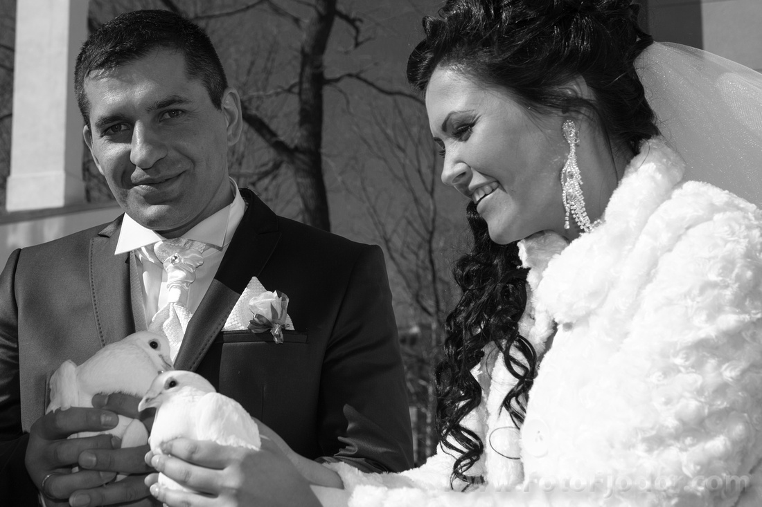 Groom and bride hold white pigeons in their hands