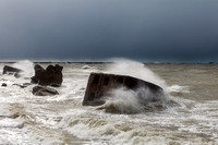 Waves crash against the forts in a stormy sea