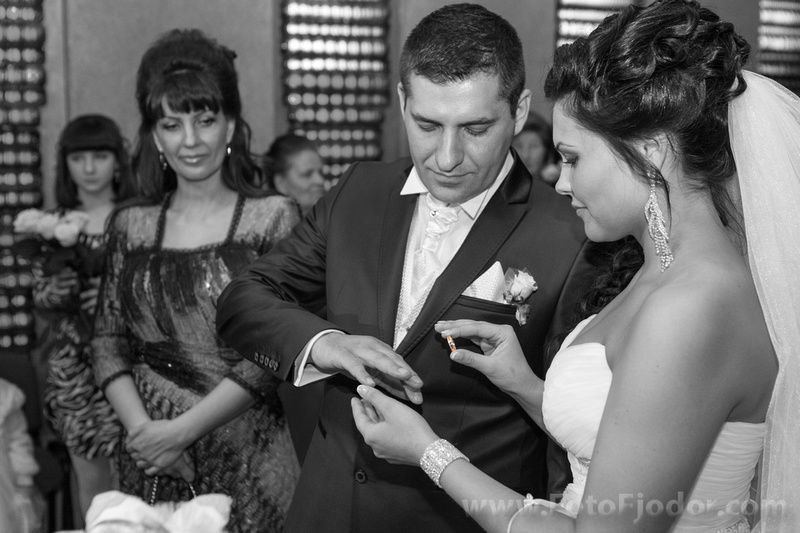Wedding ceremony: bride puts the ring on groom